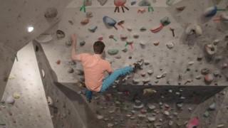 André DiFelice escalando en el rocódromo mientras entrena